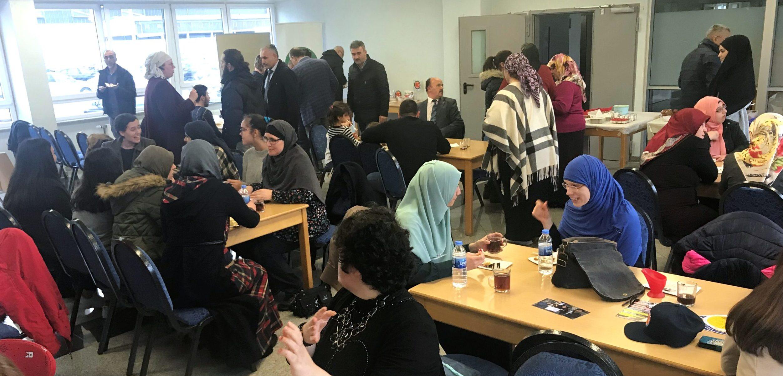 Viele muslimische Menschen stehen oder sitzen an Tischen. Sie unterhalten sich angeregt.