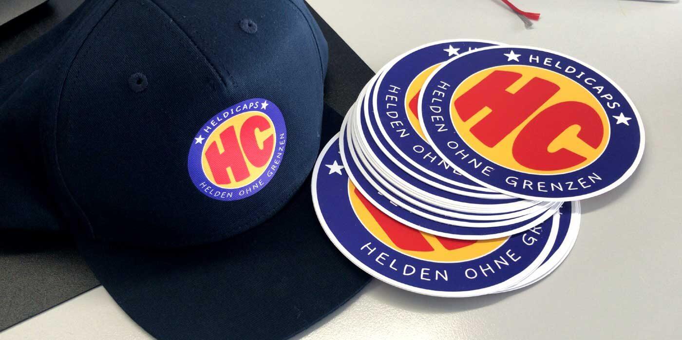 Blaue Cap mit dem Logo der Heldicaps und mehrere runde Logos aus Papier.
