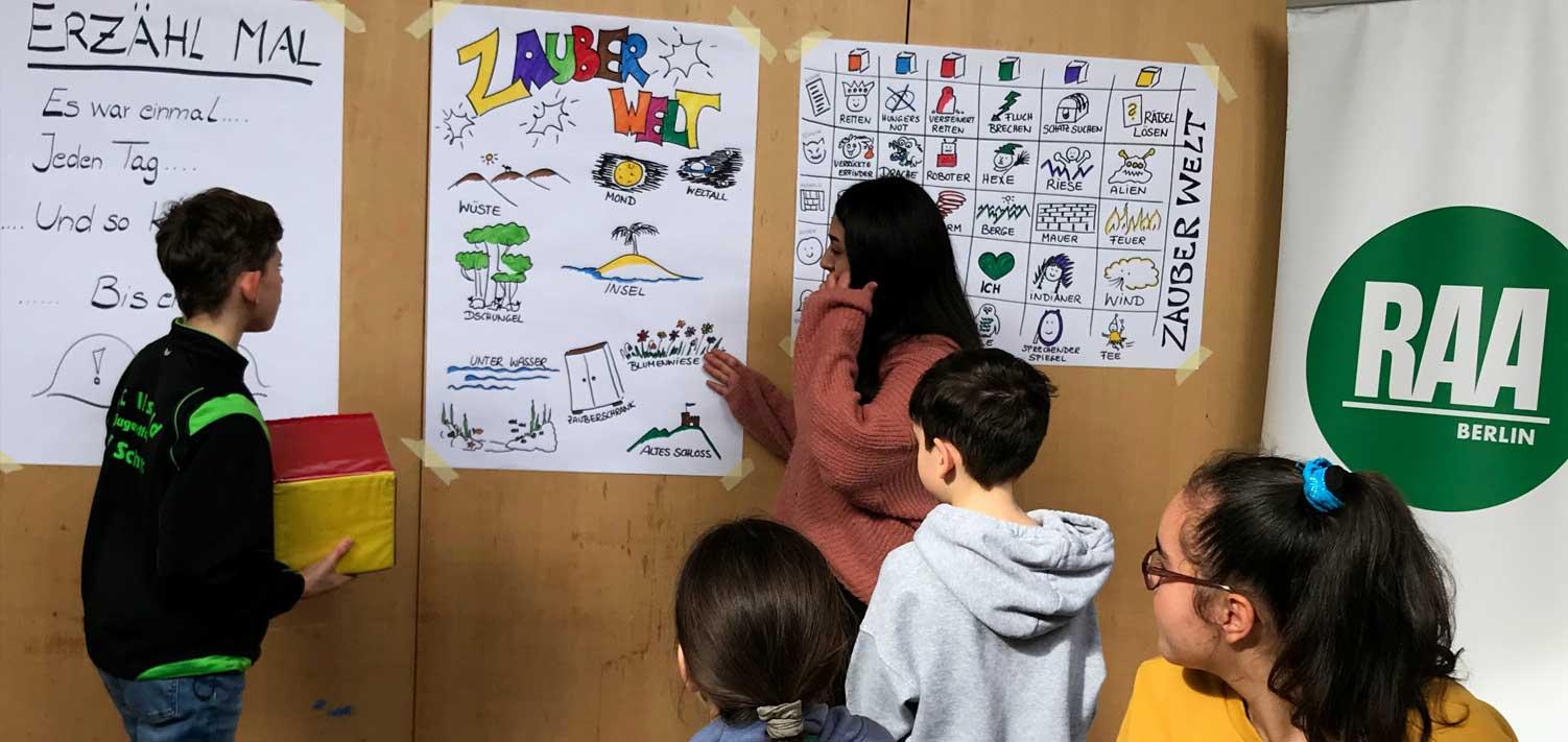 Die Kinder und Jugendlichen im Ferienprogramm: Sie spielen zusammen den Geschichtenwüfel. Bunte, große Plakate hängen an der Wand mit Symbolen, die man erwürfeln kann, um daraus eine Geschichte zu erfinden.