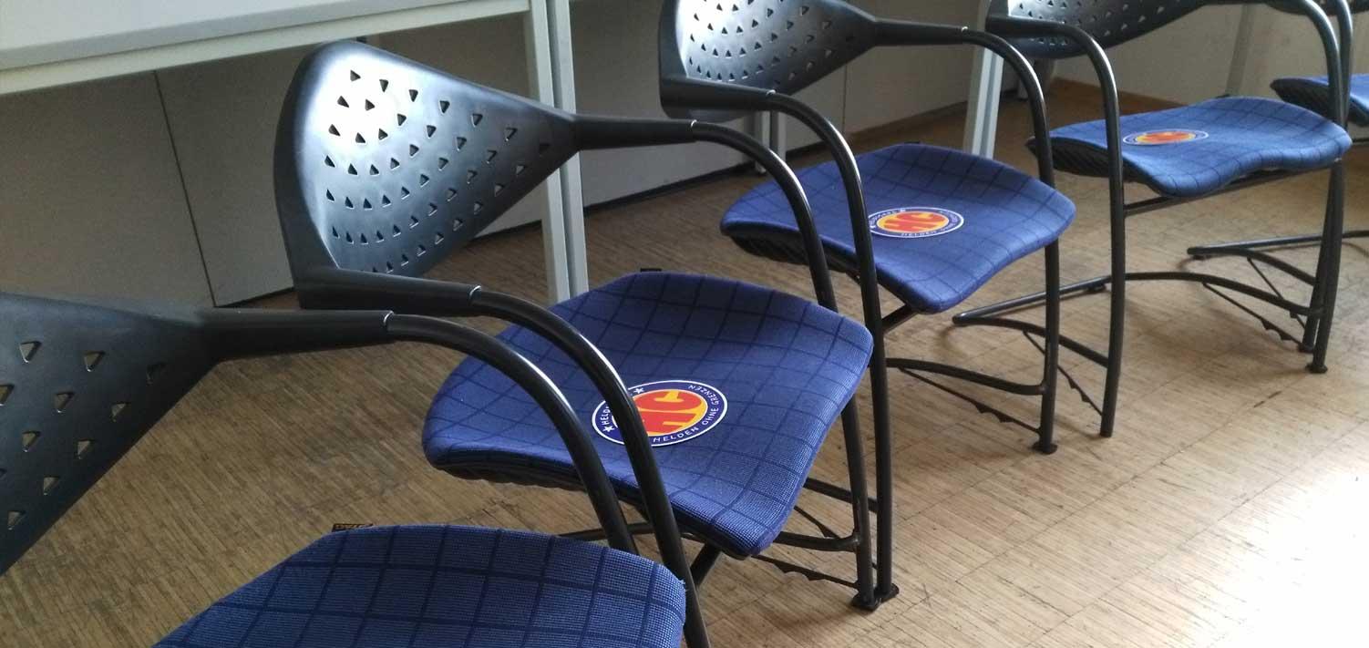 Stühle in einem Stuhlkreis. Auf jedem Stuhl liegt ein Flyer von den Heldicaps. Die Stühle sind noch leer. Es ist vor der Veranstaltung
