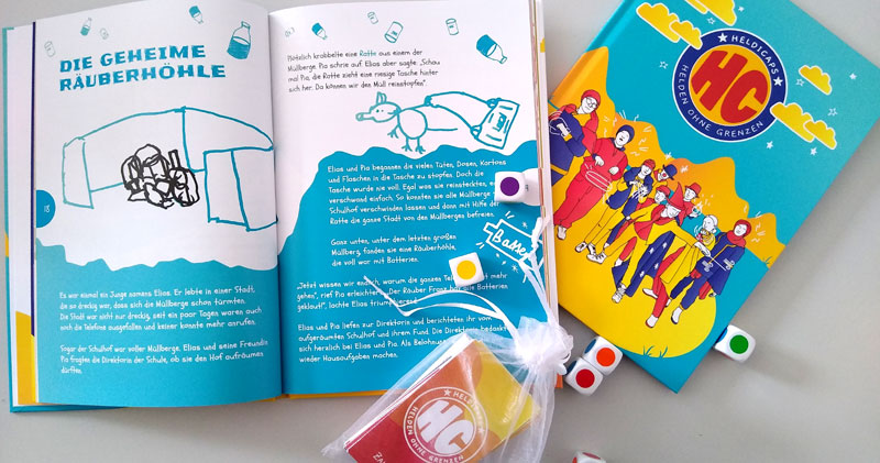 Das Buch der Heldicaps liegt aufgeschlagen auf dem Tisch, daneben noch ein geschlossenes Buch. Darauf liegt ein durchsichtiger Beutel mit den Spielkarten und einige Farbwürfel liegen verstreut herum