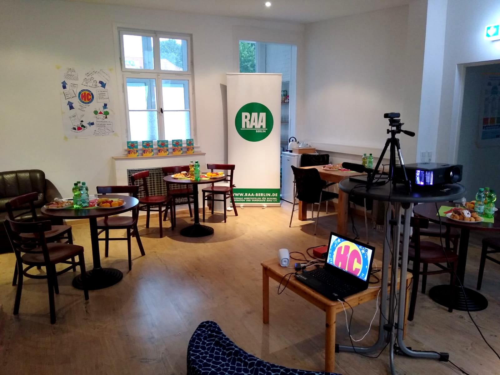 Büroraum der RAA ist festlich geschmückt. Es gibt mehrere Tische mit Snacks und Getränken, eine Kamera und einen Beamer.z ihr Heldicapsbuch und den Einheitspreis.