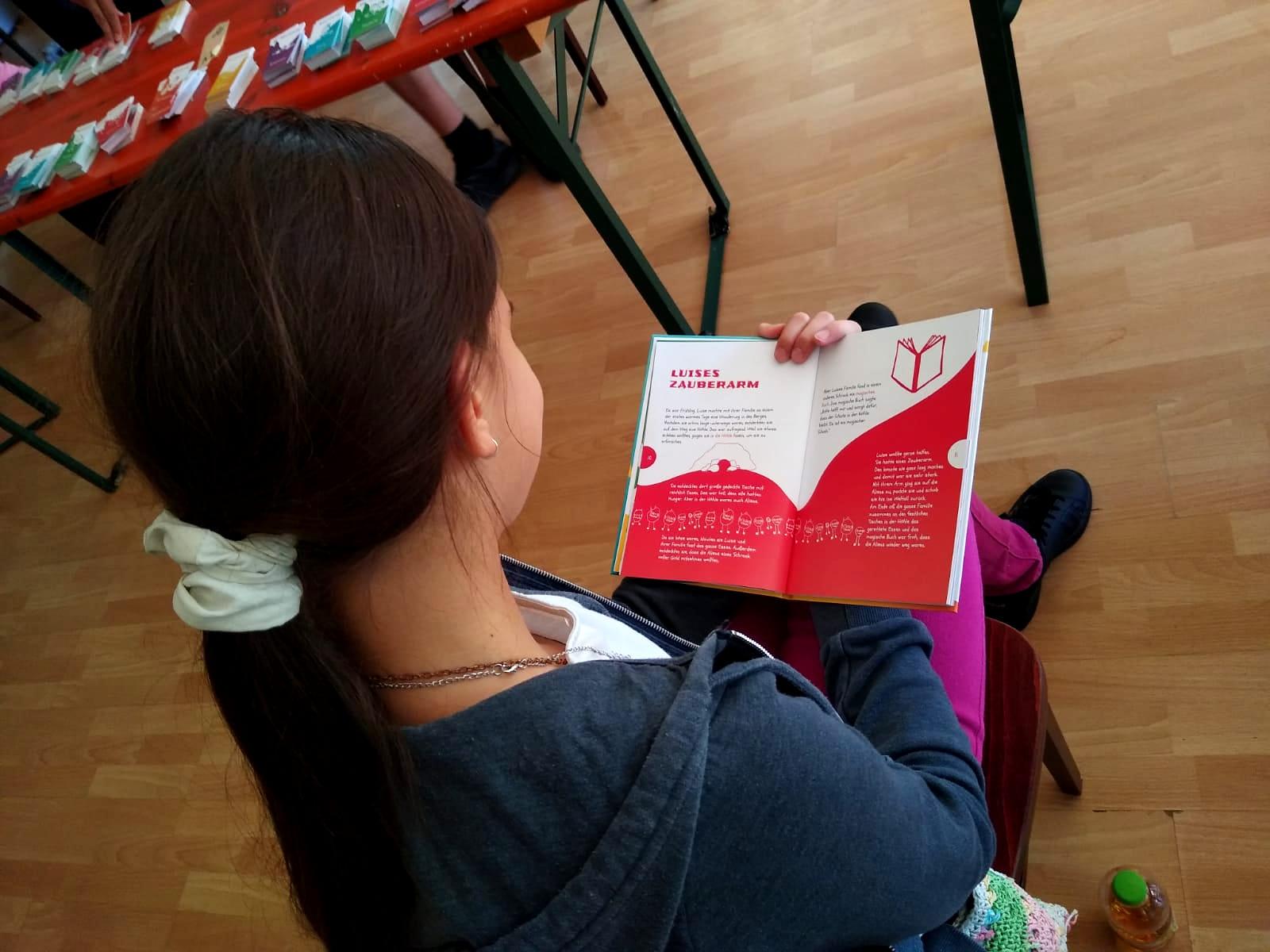 Ein Mädchen sitz auf einem Sthul und liest zum ersten Mal im Hedicaps-Buch.