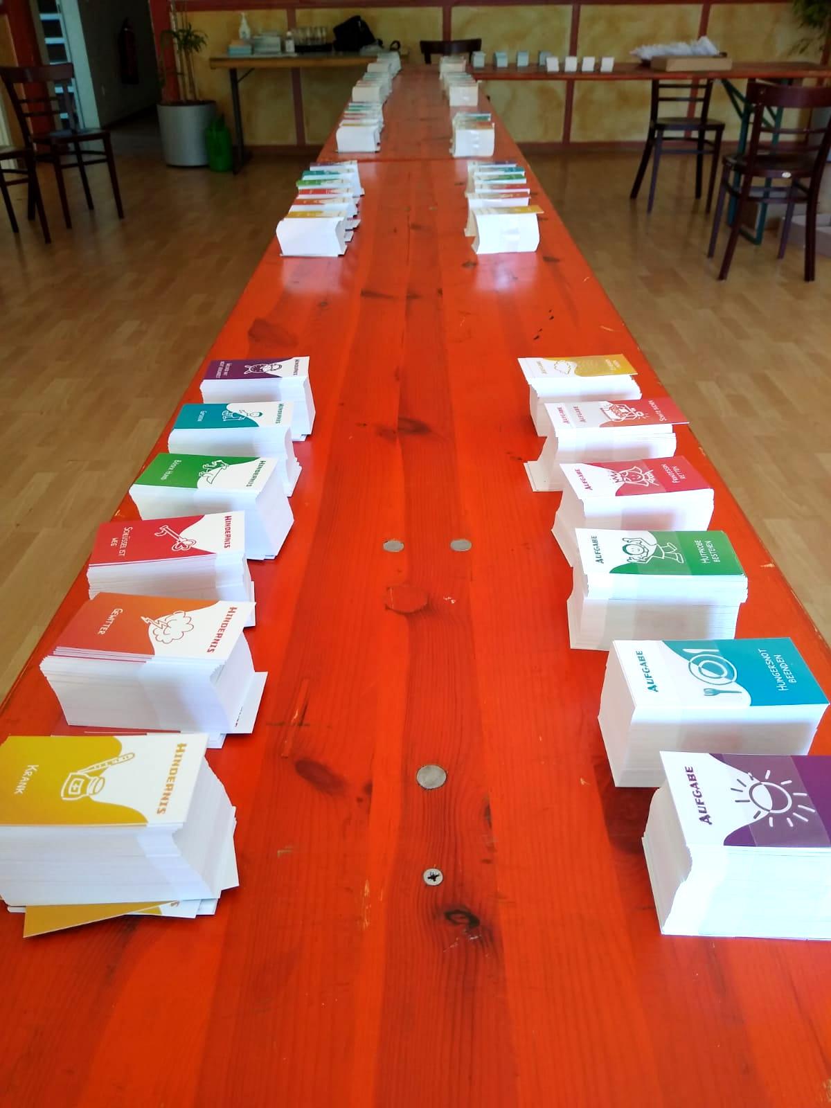 Auf einem langen Tisch stehen viele Stapel mit Zutatenkarten.