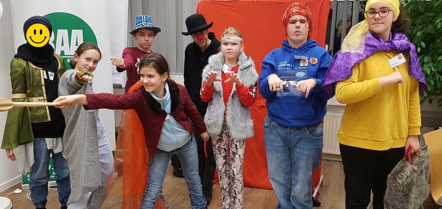 8 Kinder haben sich kostümiert und stellen pantomimisch Superhelden dar. eine Heldin trägt eine Smiley-Maske, einer ist ein mysteriöser Clown mit roter Nase und dunklem Hut, ein Kind trägt einen Turban und hat Krallenhände, ein Mädchen hat einen lila Umhang