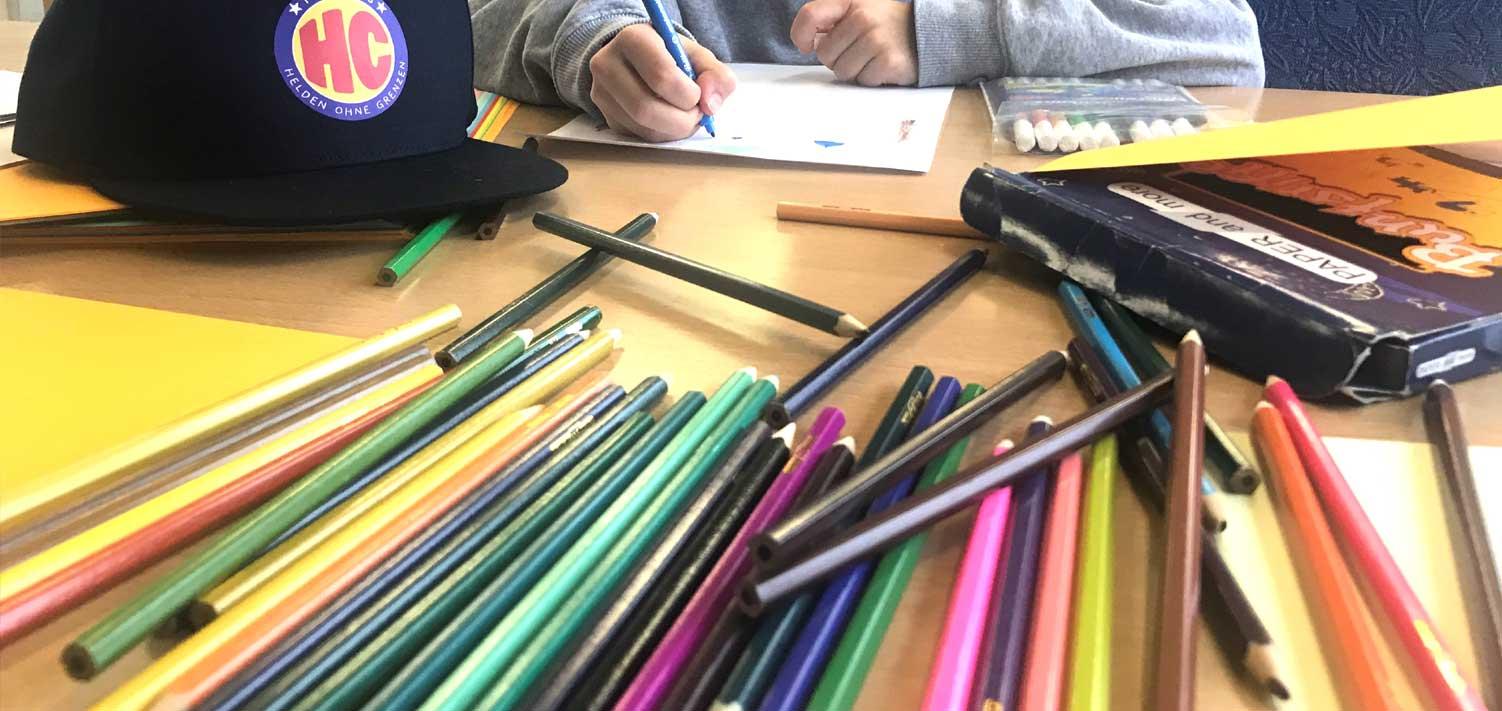 viele bunte Stifte liegen auf einem Tisch. Mit diesen Stiften malen die Kinder Bilder für ihr Buch