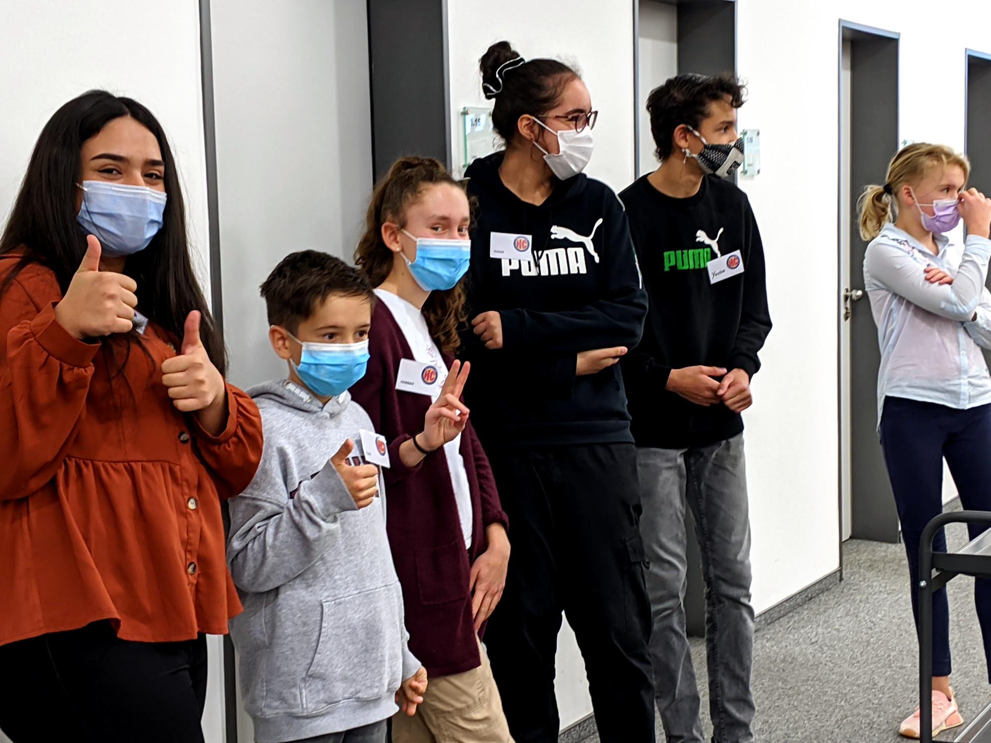 Die Heldicaps warten freudig auf den Beginn der Veranstaltung. Sie tragen Gesichtsmasken.