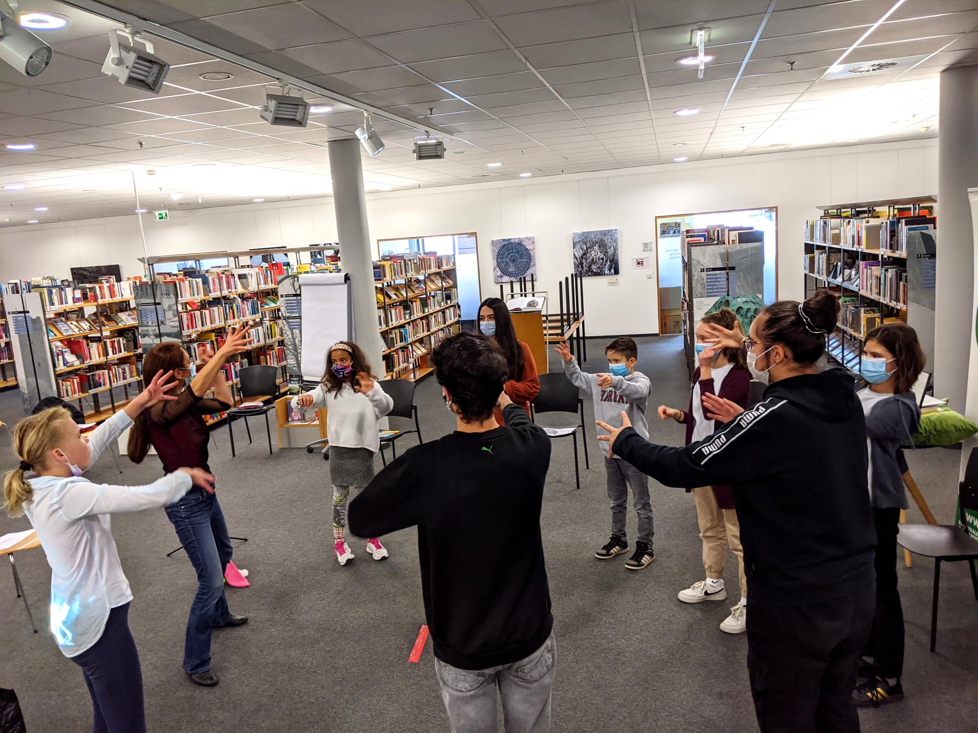 KInder und Jugendliche stehen im Kreis und machen sich warm für ihre Lesung.