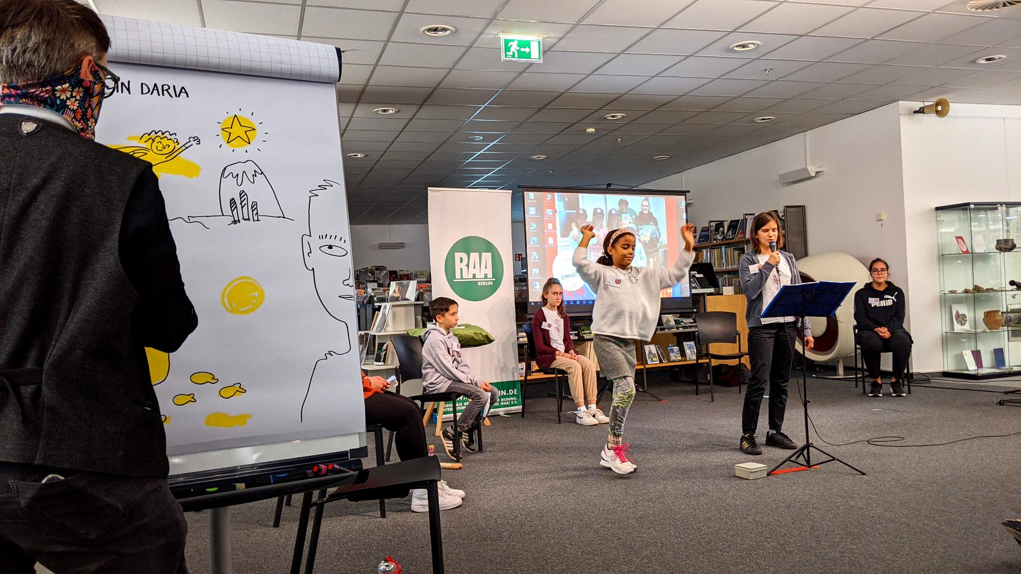 Zwei Mädchen agieren auf der Bühne. Links an der Seite zeichnet Ka Schmitz ein Bild dazu.