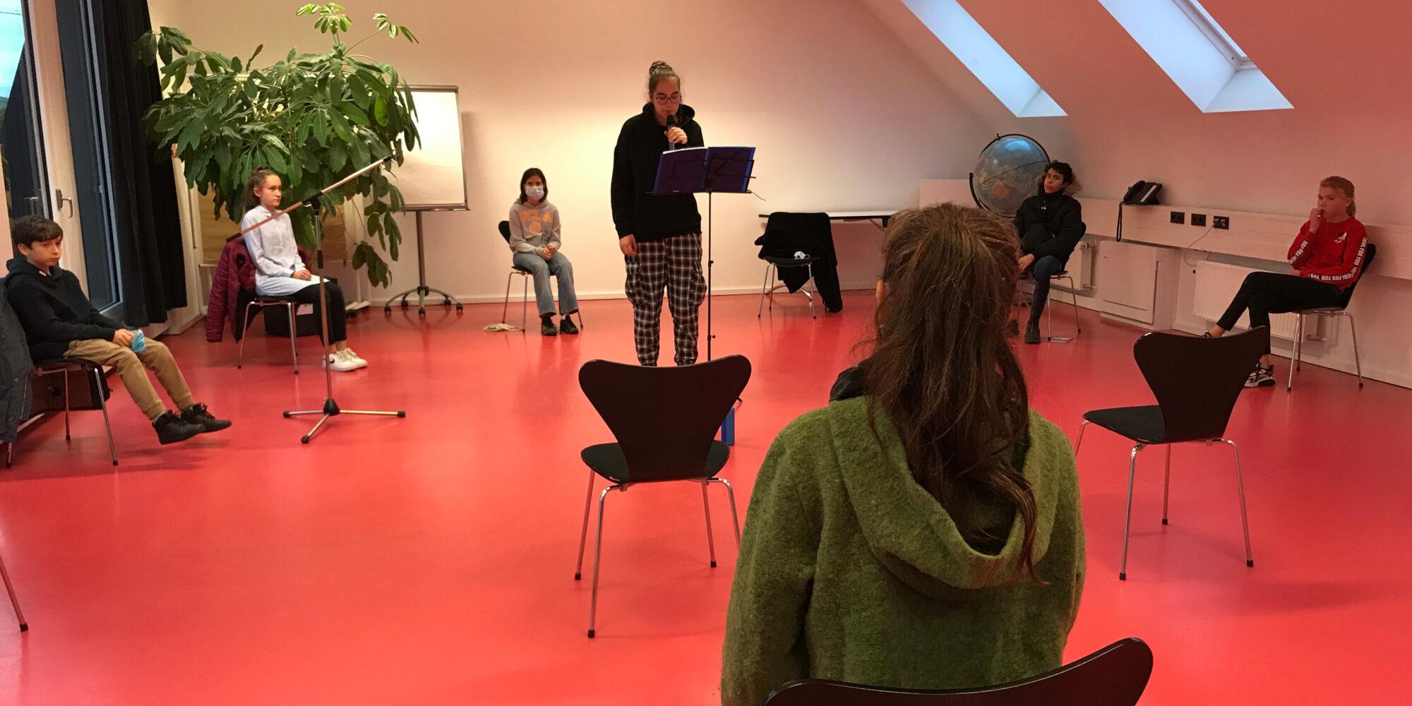 Jugendliche sitzen im Halbkreis auf einer Bühne. Ein Mädchen steht in der Mitte mit einem Mikrofon und liest eine Geschichte.