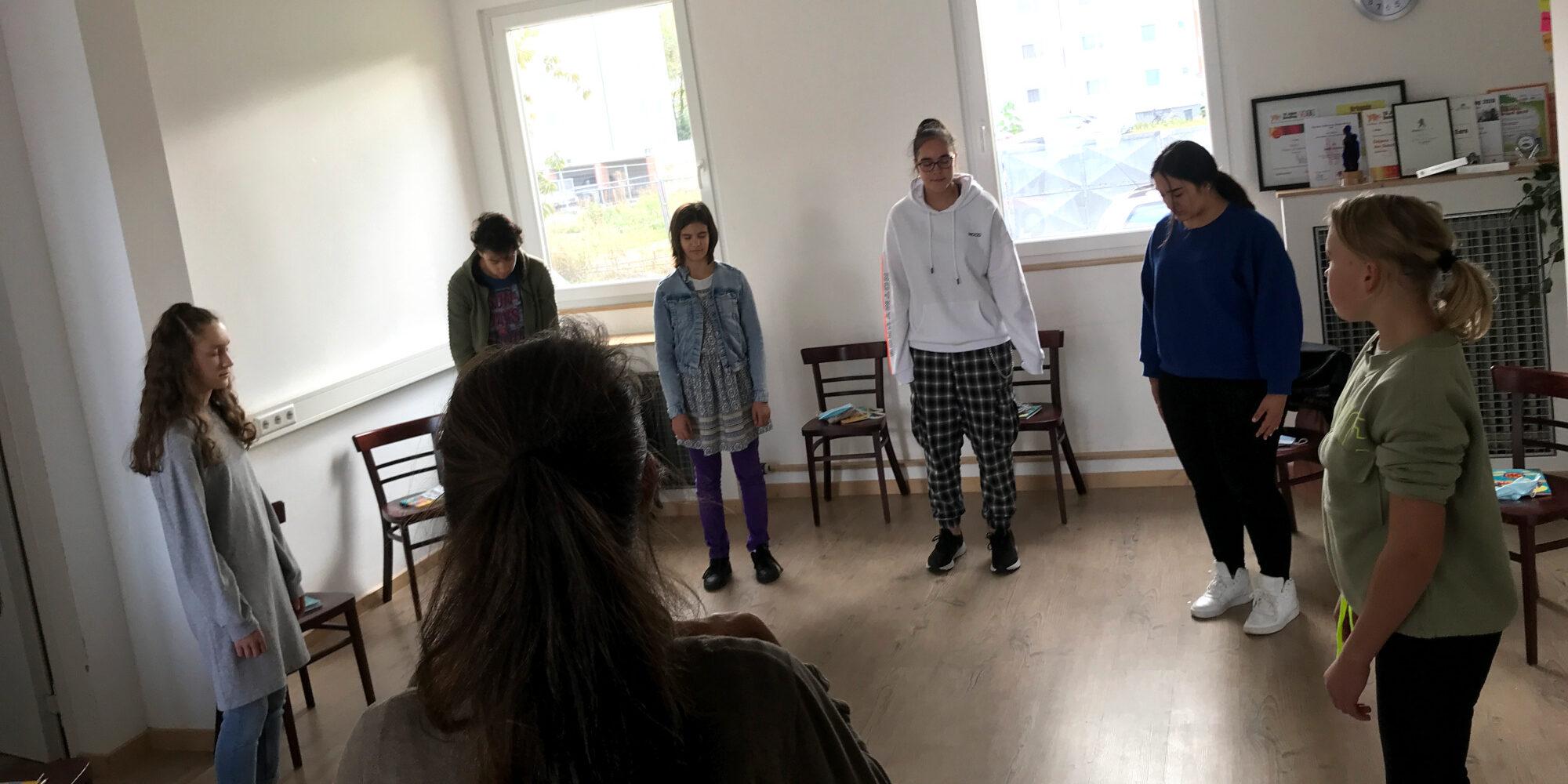 Jugendliche stehen mit geschlossenen Augen im Kreis und konzentrieren sich.