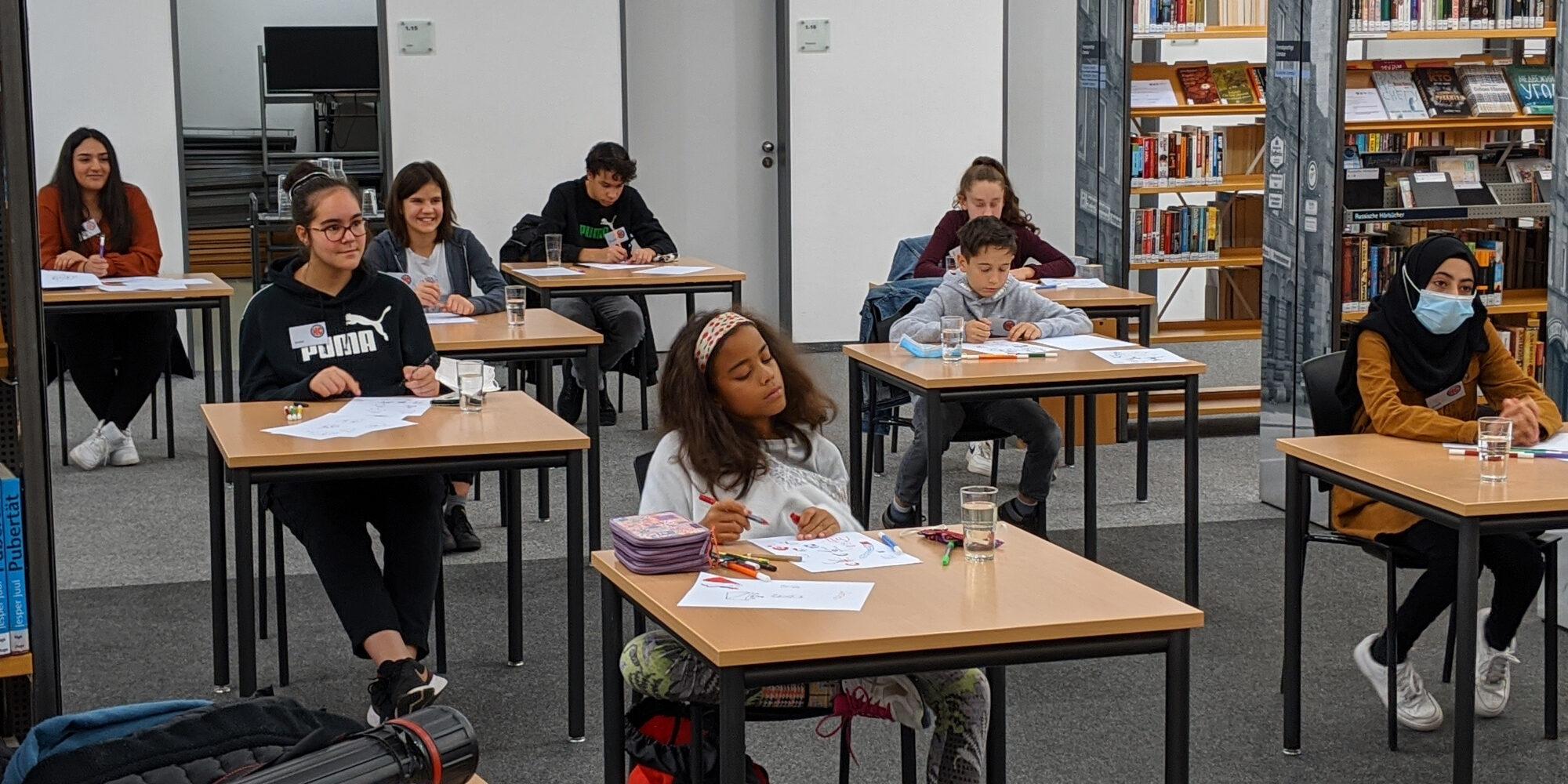 Für den Comoc-Workshop sitzen Kinder an Einzeltischen. Auf jedem Tisch liegen Stifte und Papier.