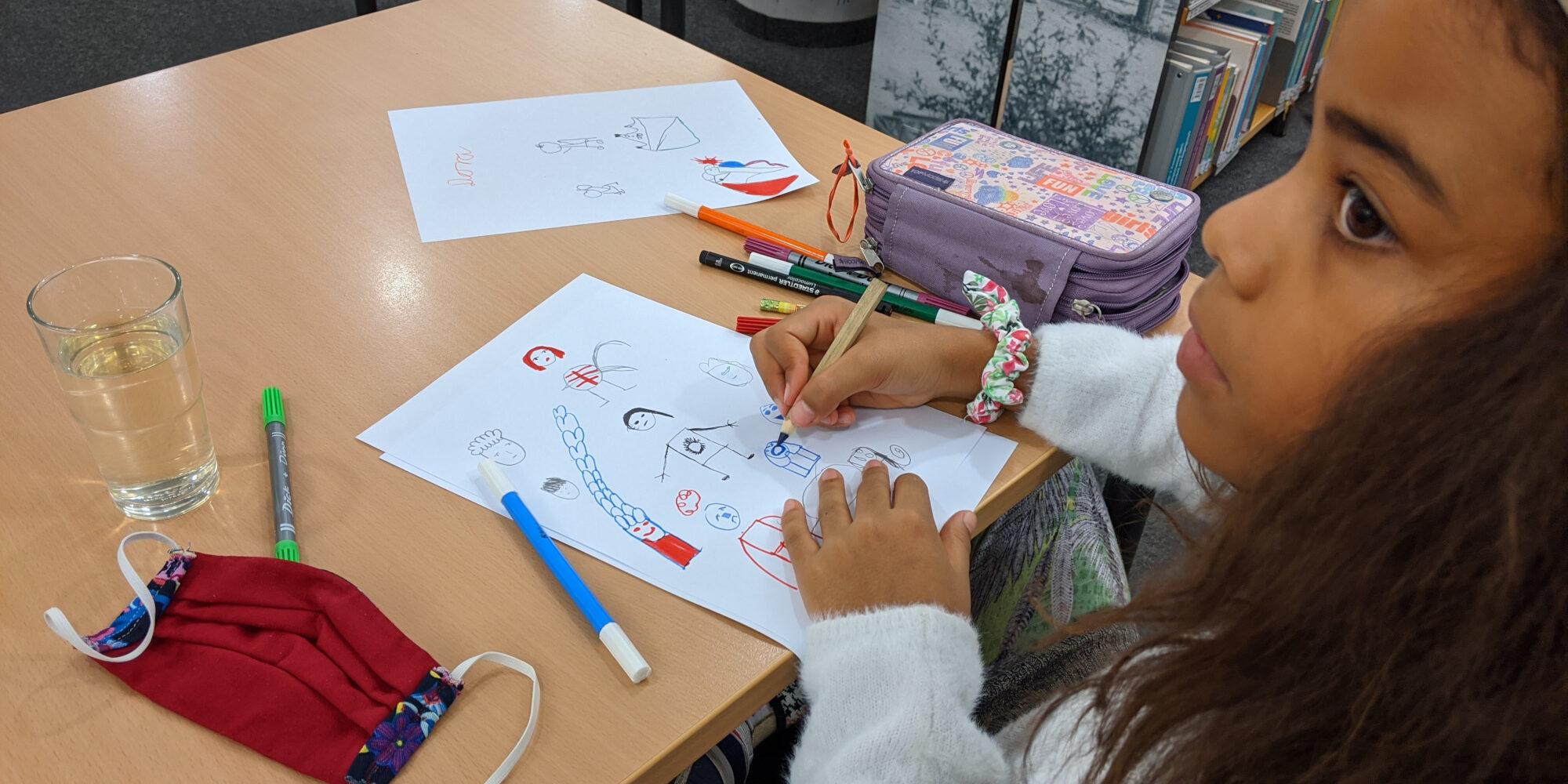 Ein Mädchen zeichnet verschiedene lustigen Figuren aufs papier.