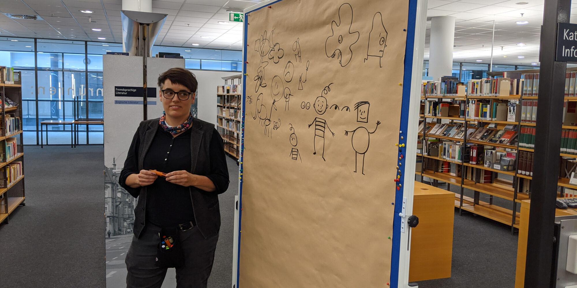 Ka Schmitz leitet den Comic Workshop. Sie steht vor einem großen Metaplanwand mit Zeichnungen.