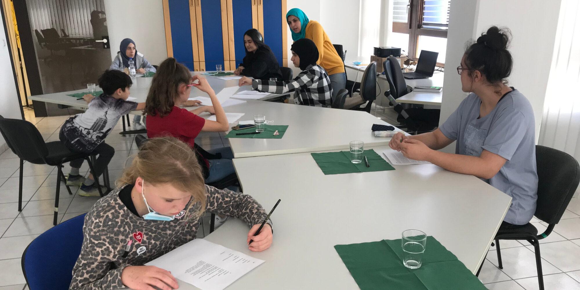 Nadia berät die Heldicaps beim Illustrieren ihrer Geschichten. Alle sitzen mit an einem großen Tisch.